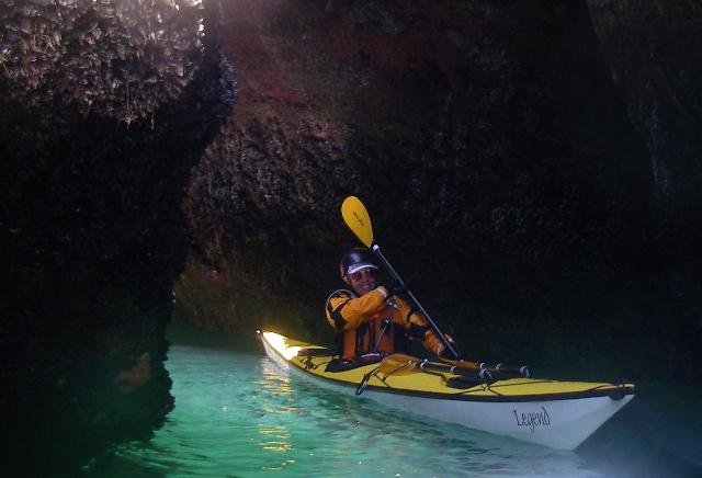 Nimble Legend sea kayak negotiates sea cave, kayak by Nigel Foster